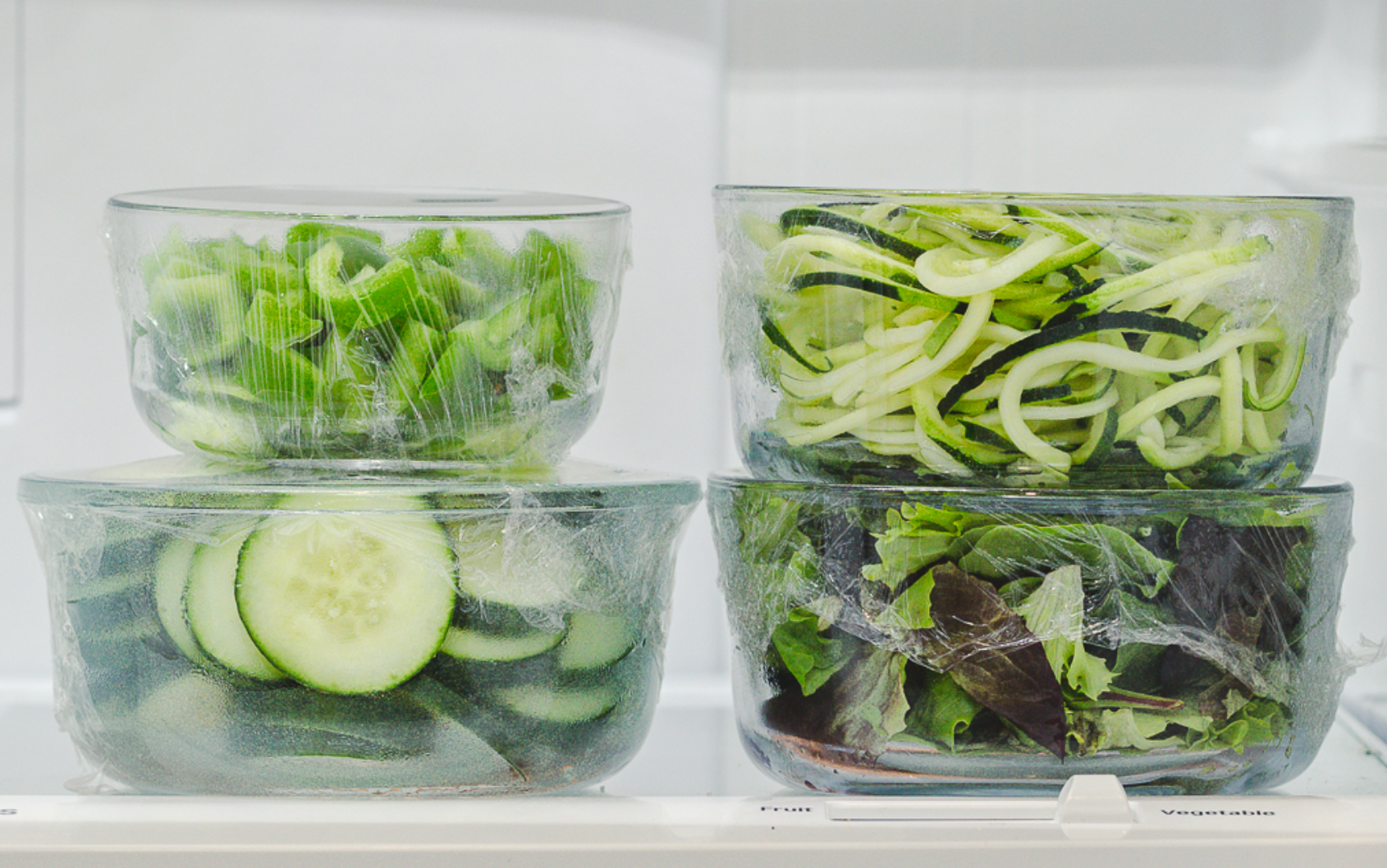 Glass food containers with salad covered with Stretch-Tite
