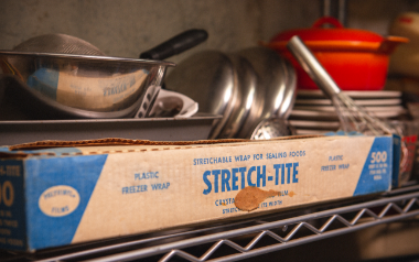 Vintage Stretch-Tite box on kitchen wire rack with pots and pans