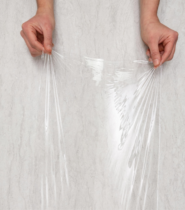 Overhead shot of hands pulling plastic wrap across counter