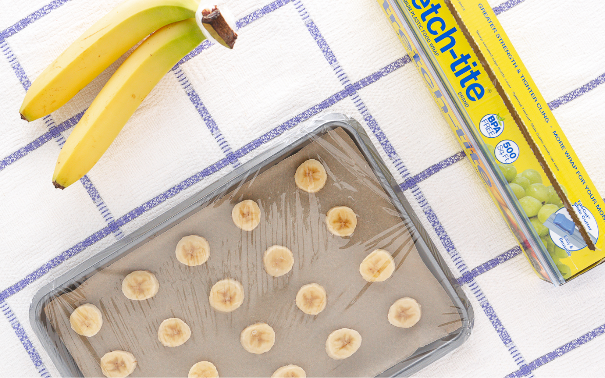 Sliced bananas on a baking sheet next to whole bananas and a box of yellow stretch-tite