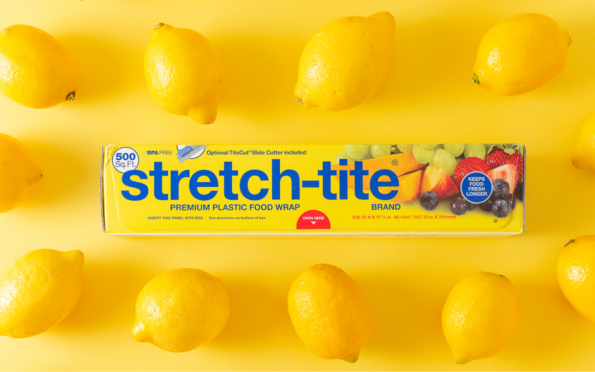 Stretch-tite box surrounded by lemons on a yellow background