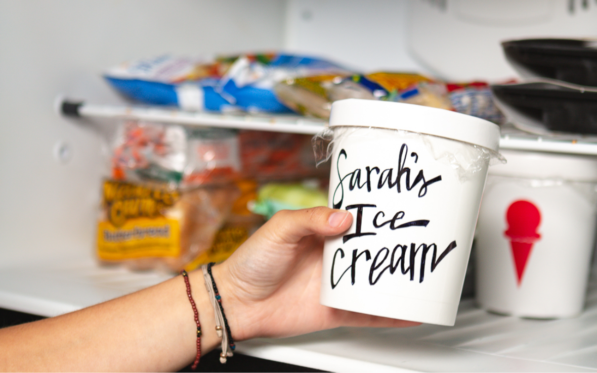 Hand in freezer pulling out Sarah's Ice Cream with Freeze-Tite