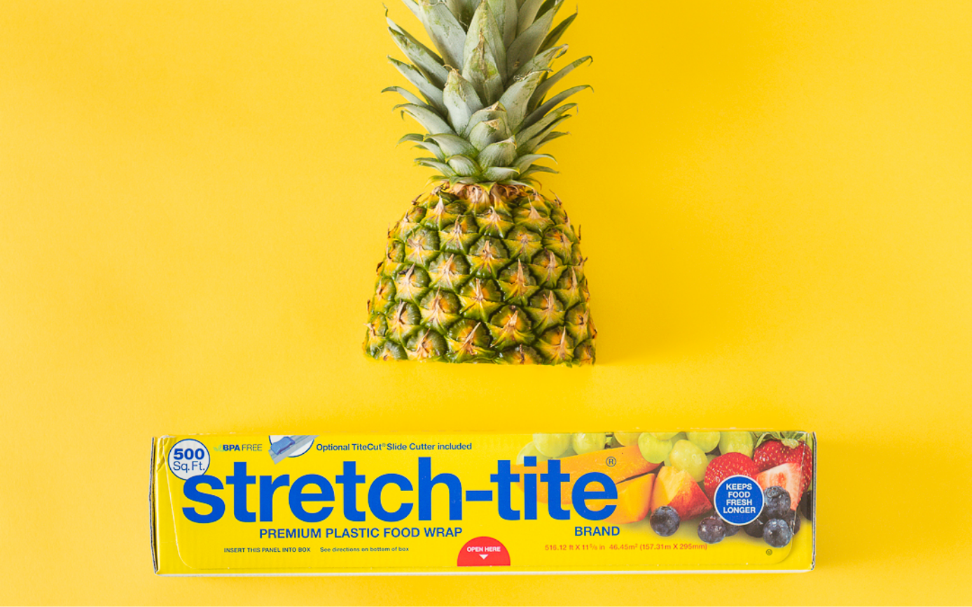 half a pineapple on yellow background with box of stretch-tite below.