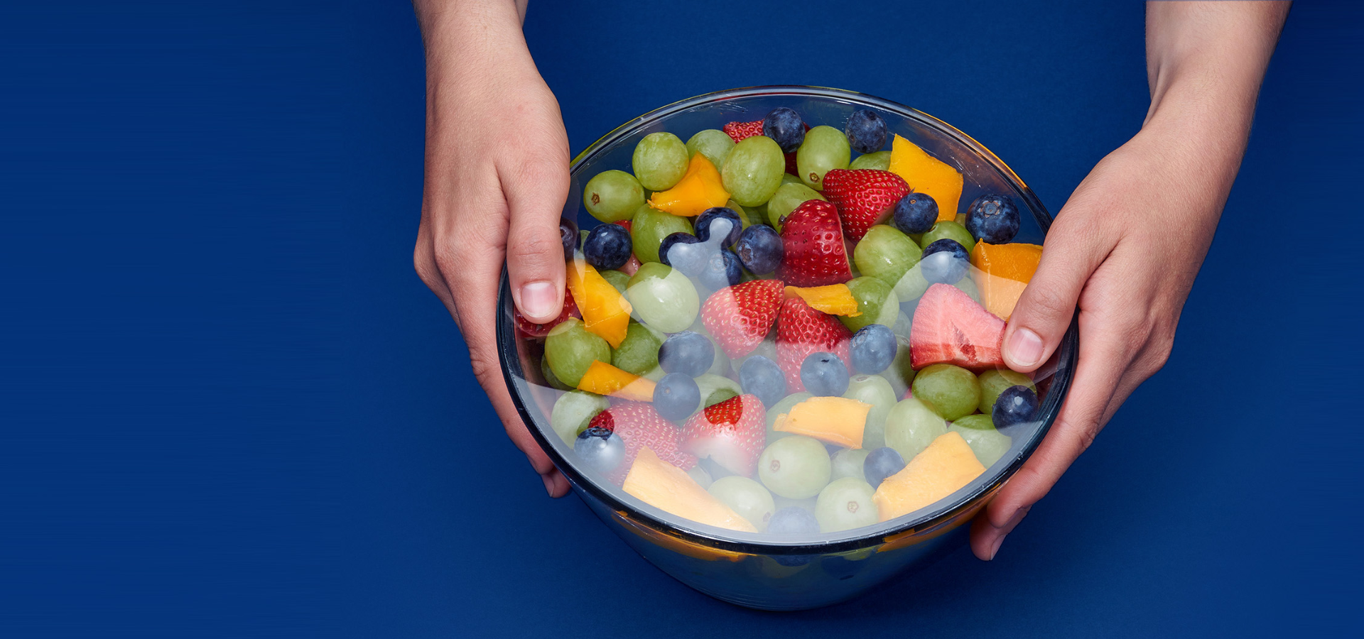 Caucasian female hands holding glass bowl with assorted fruit